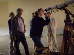 frau sieht durch schaut durch teleskop während besucher darauf warten das teleskop auch zu benutzen